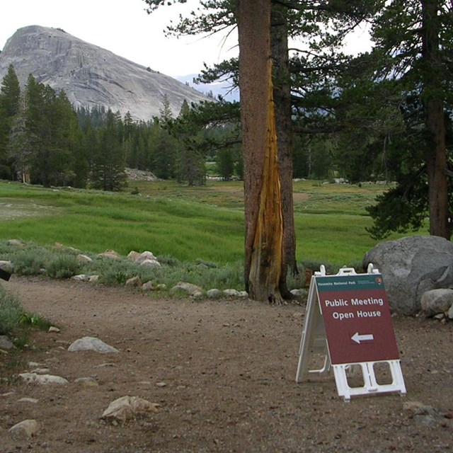 Public meeting sign near Parsons Lodge in Tuolumne Meadows with Lembert Dome in back