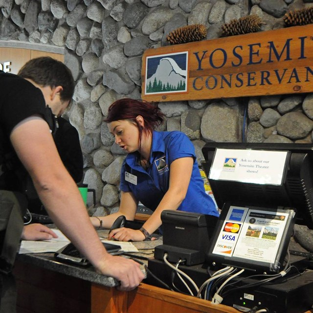 Yosemite Conservancy employee helping a visitor at the Yosemite Valley Visitor Center.