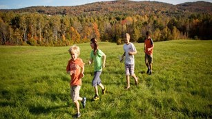 Kids running through a field.