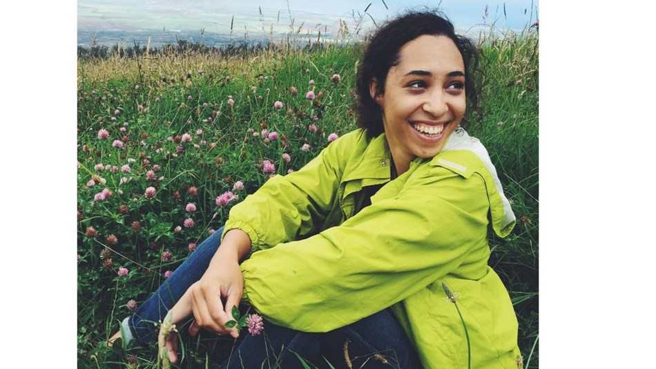 Young woman wearing a green windbreaker sits smiling in a field.