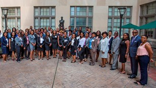 Large group of HBCUI students pose for group photo in business professional attire.