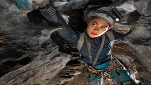 A young woman wearing a caving helmet and harness reaches forward to grab a handhold while caving.