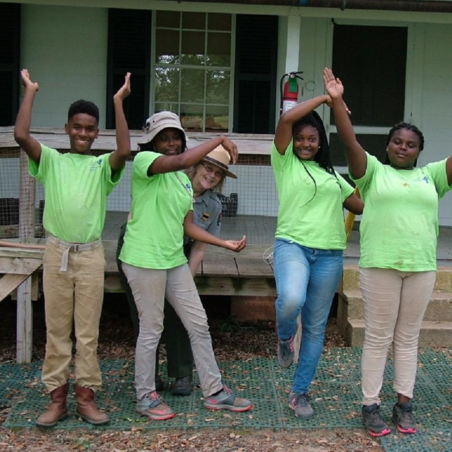 A group of Youth Conservation Corps with a ranger outside of a historic building