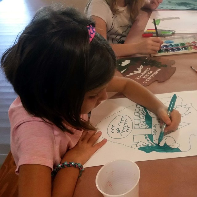 Girl scout working on art work.