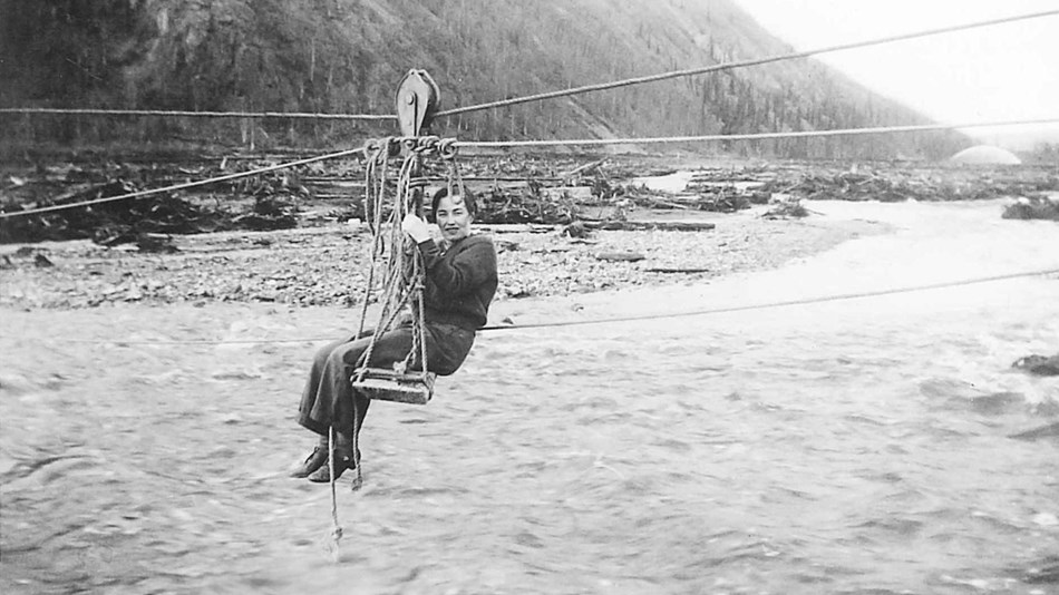 Black-and-white photo of Mildred Hendricks crossing Coal Creek on a cable hand tram