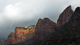 Red sandstone cliffs with grey storm clouds.