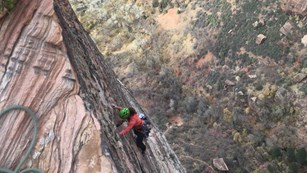 A climber scales a vertical wall high above the canyon floor.
