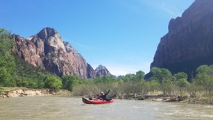 Visitors float down a river between towering canyon walls in an inflatable kayak.