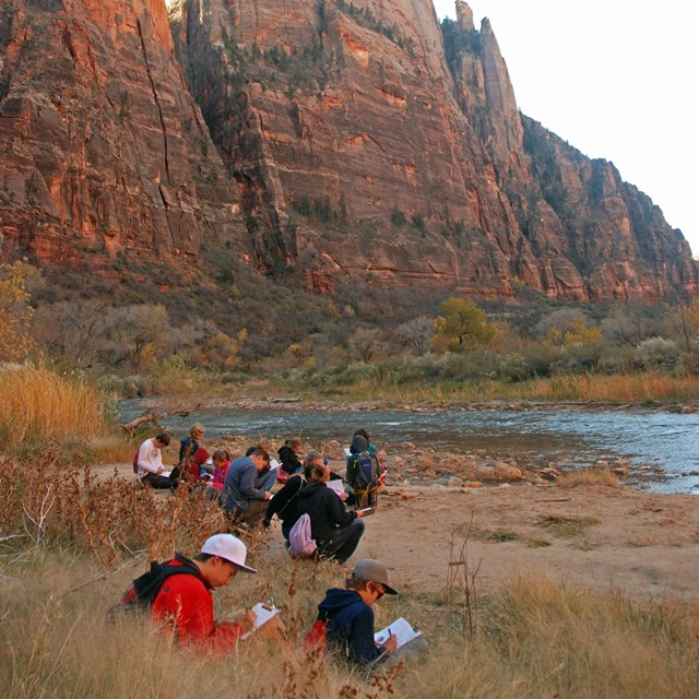 Students writing in notebooks along a river bank