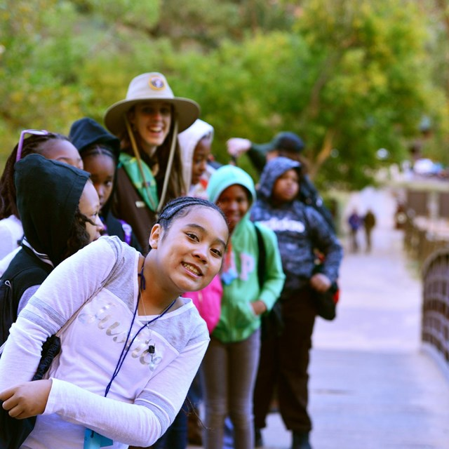 students walking on a bridge over a stream