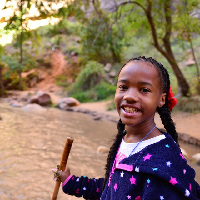 A student hiking in the river