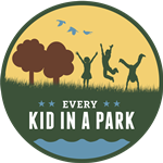 Colorful circular logo for Every Kid in a Park shows grass, trees, and the silhouettes of children playing