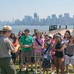 Park Ranger speaks to a group of students. New York City skyline in the background.