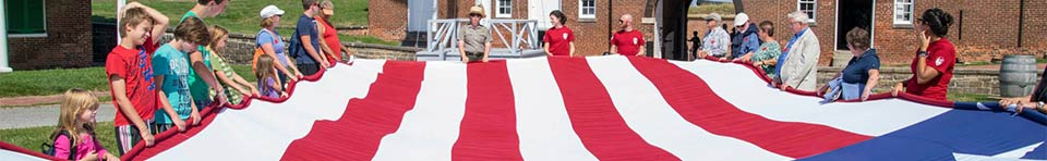 Large American Flag is held open by a Park Ranger and a number of visitors