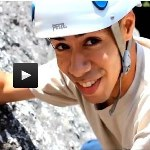 Young boy rock climbing and smiling.
