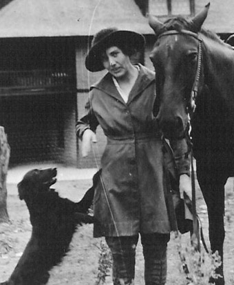 Lillian Erickson Riggs standing between a dog and a horse at Faraway Ranch