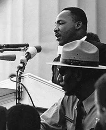 B&W photo of MLK at podium with park ranger seated below