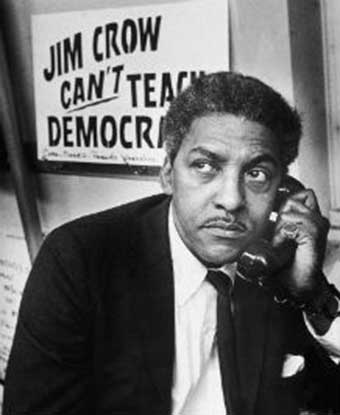 Mr. Rustin on the phone with 'Jim Crow Can't Teach Democracy' sign behind him