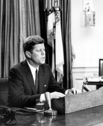 B&W photo of JFK seated at desk with microphone addressing nation