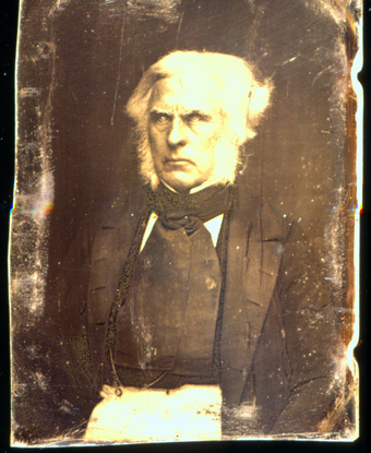 Photograph of Dr. John McLoughlin wearing a dark-colored suit and cravat.
