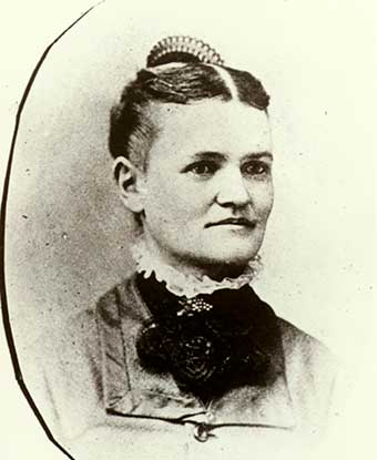 A 1879 portrait photo depicts a woman in a dress with parted hair and a comb.