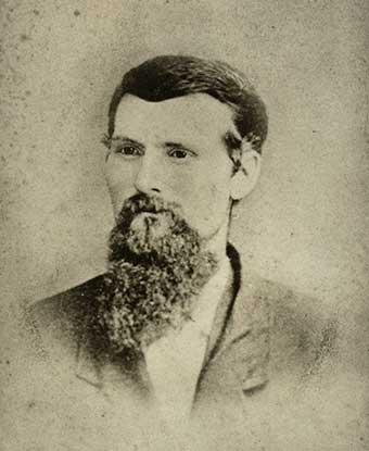 An 1879 portrait photo depicts a bearded man in a suit jacket.