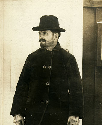 A 1904 photograph shows a rugged man outdoors in a hat and winter coat.