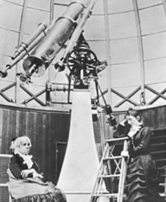 Two women working at a large telescope