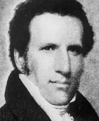 Black and white bust-length portrait of a man with dark hair, wearing a high white collar.