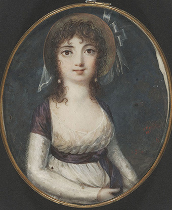 Color image of a waist-length portrait of a young woman with large eyes and dark hair.
