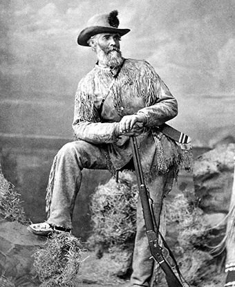 Norris wearing a frilled leather jacket and pants, a hat, and leaning against a rifle.