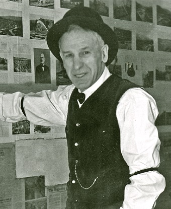 A man in a vest, white shirt, and hat.