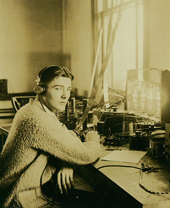 A 1921 photograph depicts a young man at a table operating radio equipment.
