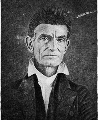 black and white image of John Brown; he's clean shaven; wearing a white collared shirt and dark coat