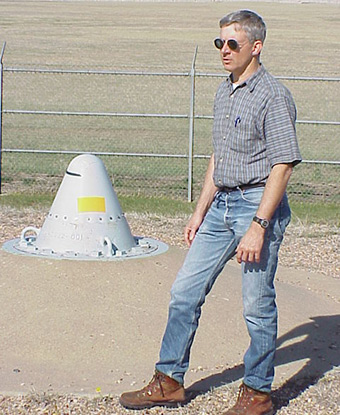 Man stands next to a metal cone in the ground