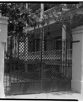 Property gate with house in background.