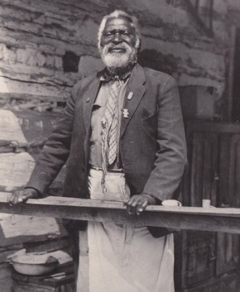 Photo of elderly man with white beard standing on cabin porch.