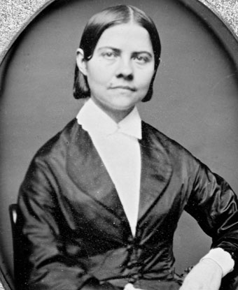 Black and white photograph of Lucy Stone wearing a dark jacket with white shirt and collar.