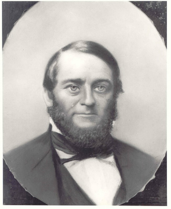 black and white portrait photograph of a middle aged white man with a full beard wearing a suit