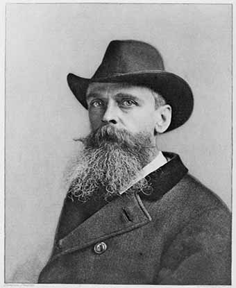 Black and white image of a man wearing an overcoat and hat with a long beard.