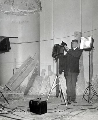 Black and white image of man photographing interior renovation of a building