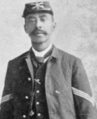 A soldier wearing a dark colored uniform and brimmed hat