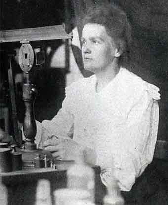 Marie Curie looks into a scientific instrument