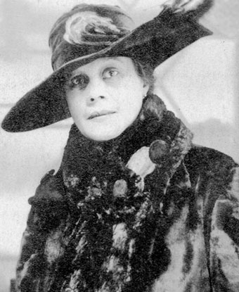 A woman wearing a large hat with feathers and a fur coat