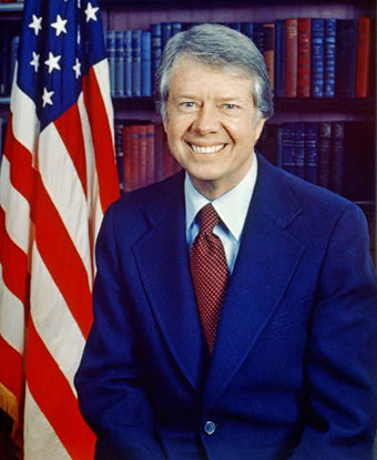 Jimmy Carter, head-and-shoulders portrait, facing front, next to an American flag