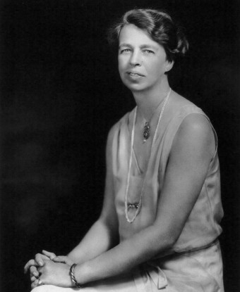 A seated woman (Eleanor Roosevelt) wearing a sleeveless gown and a string of pearls.