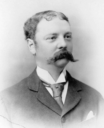 A head and shoulders portrait of a man with mustache wearing a suit.