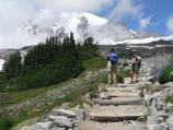 Hikers stand on a rocky trail amid subalpine meadows with Mount Rainier in the background.
