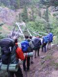 A line of hikers approach a trestle bridge