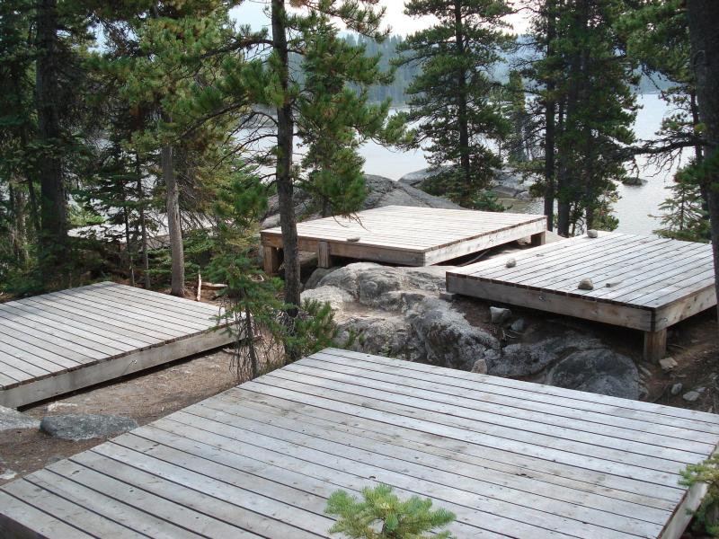 Wooden tent platforms among trees in front of a lake